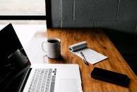 Auf einem Holztisch liegen und stehen ein Laptop und Schreibutensilien